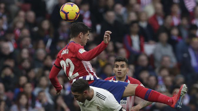 Bek Real Madrid, Sergio Ramos, berebut bola dengan striker Atletico Madrid, Alvaro Morata, pada laga La Liga di Stadion Wanda Metropolitano, Sabtu (9/2). Real Madrid menang 3-1 atas Atletico Madrid. (AP/Manu Fernandez)
