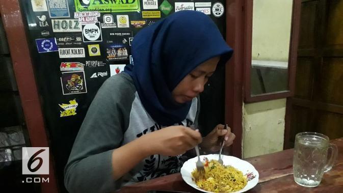 Seorang pelanggan sedang menyantap mi goreng di warung Mie Nyemek Bu Siti (Liputan6.com/Komarudin)