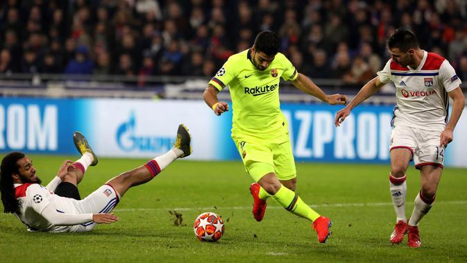 Penyerang Barcelona Luis Suarez (tengah) menggiring bola melewati bek Lyon Jason Denayer dan Leo Dubois pada leg pertama babak 16 besar Liga Champions di Decines, Lyon, Prancis, Selasa (19/2). Laga berakhir 0-0. (AP Photo/Laurent Cipriani)