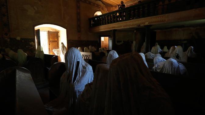Gambar pada 30 Agustus 2018 menunjukkan  turis Prancis mengambil gambar patung-patung serupa hantu yang ditampilkan di Gereja St George, Lukova, Republik Ceko. Ibadah terakhir yang diadakan di dalam gereja berlangsung di tahun 1968. (AP/Petr David Josek)