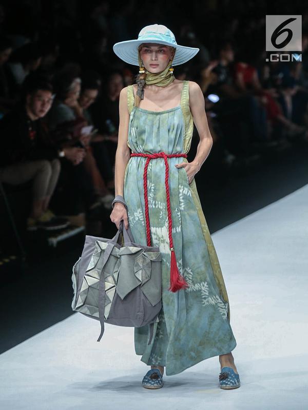 Model memperagakan busana rancangan HUMBANG SHIBORI x PURANA saat Jakarta Fashion Week 2019 di Senayan City, Jakarta, Kamis (25/10). Tenun ikat Humbang Shibori merupakan kerajinan kriya yang dibuat dengan metode ikat celup. (Liputan6.com/Faizal Fanani)