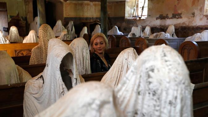 Turis Prancis mengunjungi Gereja St George yang menampilkan patung-patung serupa hantu di Lukova, 30 Agustus 2018. Membuat banyak orang penasaran, gereja yang terbengkalai ini justru menjadi destinasi wisata mistis menarik di Ceko. (AP/Petr David Josek)