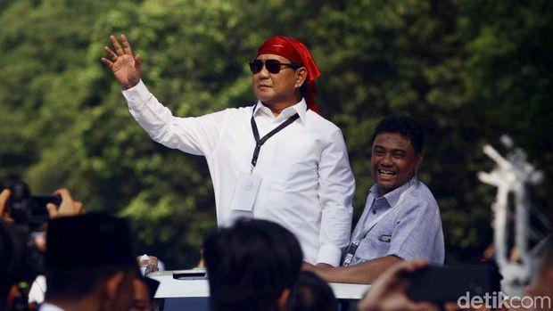 Prabowo menyapa pendukung dari sunroof mobil.