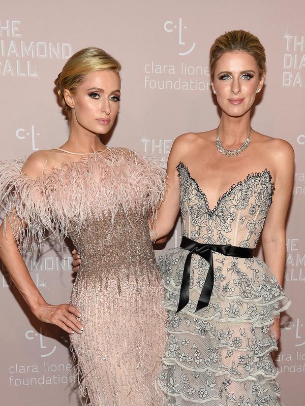 Model dan sosialita Paris Hilton (kiri) dan Nicky Hilton Rothschild saat menghadiri Diamond Ball ke-4 di Cipriani Wall Street, New York, AS, Kamis (13/9). Keduanya tampil dengan gaun merah dan biru. (Dimitrios Kambouris/GETTY IMAGES NORTH AMERICA/AFP)