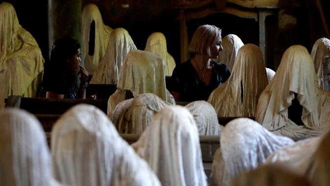 Turis Prancis mengambil gambar patung-patung serupa hantu yang ditampilkan di Gereja St George, Republik Ceko, 30 Agustus 2018. Patung-patung ini merepresentasikan hantu Sudeten Jerman yang hidup di Lukova sebelum Perang Dunia II. (AP/Petr David Josek)