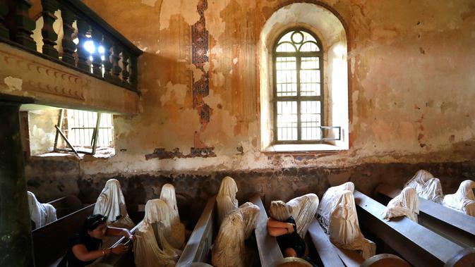 Gambar pada 30 Agustus 2018, turis Prancis mengunjungi Gereja St George yang menampilkan patung-patung serupa hantu di Lukova, Ceko. Dengan interior gereja yang sudah lapuk, tempat ini sukses menarik perhatian wisatawan dunia. (AP/Petr David Josek)
