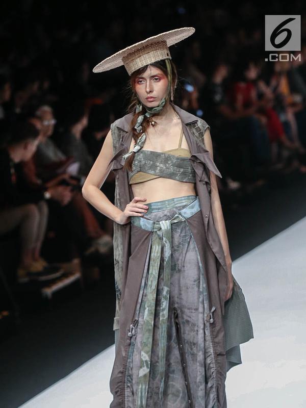Model memperagakan busana rancangan HUMBANG SHIBORI x PURANA saat Jakarta Fashion Week (JFW) 2019 di Senayan City, Jakarta, Kamis (25/10). HUMBANG SHIBORI x PURANA mengangkat tenun ikat tradisional Humbang Shibori. (Liputan6.com/Faizal Fanani)