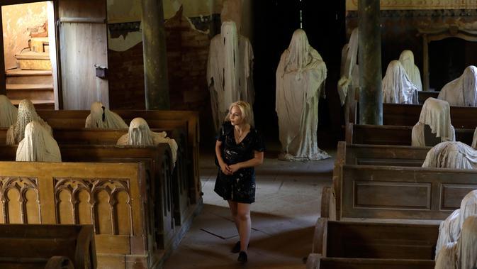 Turis Prancis mengunjungi Gereja St George yang menampilkan patung-patung serupa hantu di Lukova, Republik Ceko, 30 Agustus 2018. Selusinan patung menyerupai manusia berselimut jubah itu ditaruh berjajar seperti sedang mengikuti misa (AP/Petr David Josek)