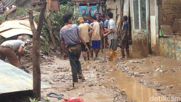 Warga, petugas Damkar dan Satpol PP bersih-bersih permukiman dari lumpur di Kampung Arus, Cawang, Jaktim, Kamis (8/2/2018)