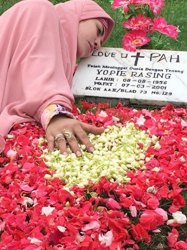 Penyanyi dangdut Cinta Penelope saat nyekar ke makam ayahandanya. Mantan istri Mustafa Debu ini telah menutup auratnya dengan hijab panjang.  (Instagram/princess_cinta_penelope)