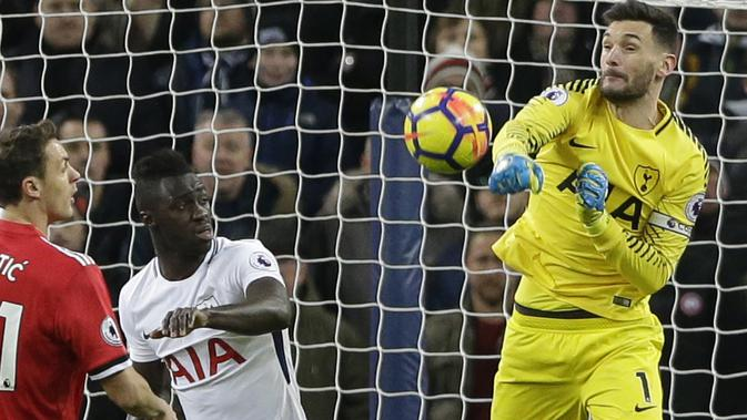 Kiper Tottenham, Hugo Lloris meninju bola dari kejaran pemain Manchester United, Nemanja Matic (kiri)  pada lanjutan Premier League di Wembley stadium, (31/1/2018). Spurs menang 2-0. (AP/Alastair Grant)