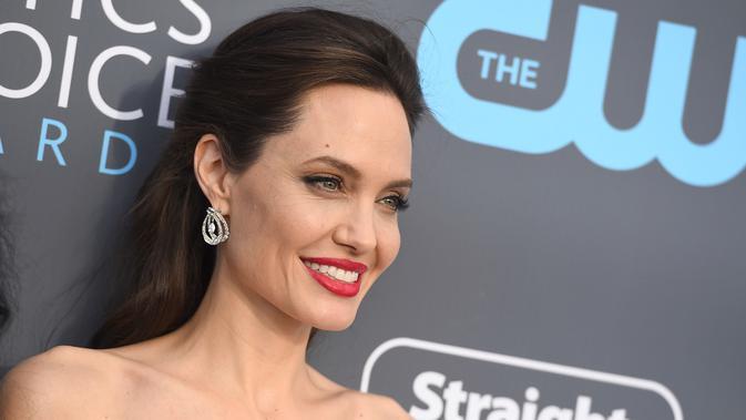 Angelina Jolie menghadiri acara Critics Choice Awards 2018 di Santa Monica, California, Kamis (11/1). Angelina Jolie pun menghias wajahnya dengan makeup klasik yang berfokus pada eyeliner dan lipstik merah merona. (Jordan Strauss/Invision/AP)