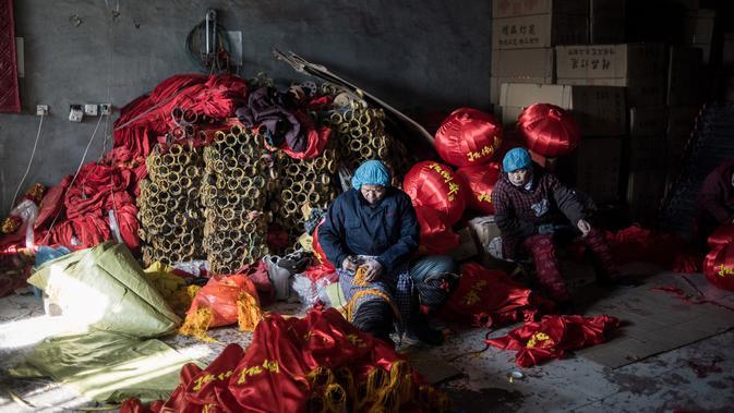 Pekerja membuat rumbai-rumbai untuk lampion merah yang akan dijual menyambut perayaan Tahun Baru Imlek di provinsi Hebei, Tingkok (11/1). (AFP Photo/Fred Dufour)