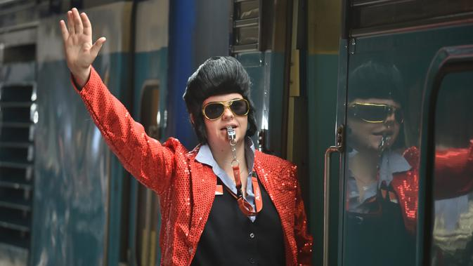 Kondektur kereta berpakaian seperti Elvis memberi isyarat agar kereta meninggalkan stasiun Central untuk membawa orang ke Parkes Elvis Festival, di Sydney (11/1). (AFP Photo/Peter Parks)