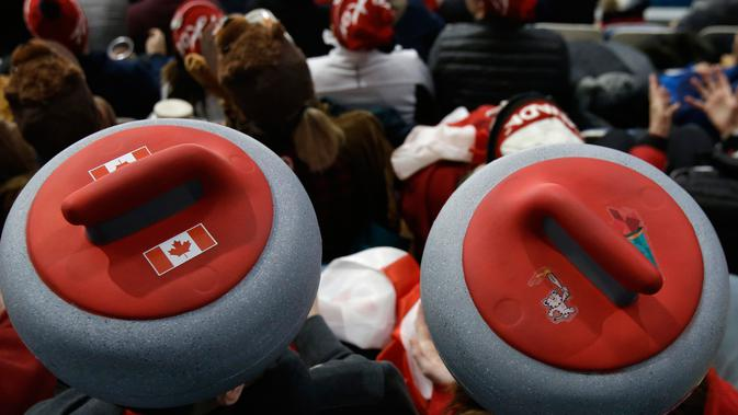 Penonton mengenakan atribut kepala unik saat menyaksikan cabang curling ganda campuran antara Kanada dan Swiss pada Olimpiade Musim Dingin 2018 di Gangneung, Korsel, Selasa (13/2). Olimpiade ini berlangsung hingga 25 Februari mendatang. (AP/Aaron Favila)
