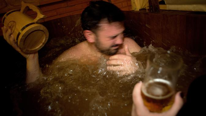 Pengunjung menikmati berendam di bak pemandian penuh bir di Beer Spa of Spain yang pertama kali dibuka di Granada, Spanyol, Selasa (13/2). Tempat spa bir itu juga memberikan bir gratis kepada para tamu selagi mereka berendam. (JORGE GUERRERO/AFP)