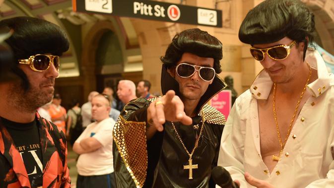 Sejumlah penggemar Elvis mengenakan kostum berpose saat berfoto bersama sebelum naik kereta ke The Parkes Elvis Festival, di Sydney (11/1). (AFP Photo/Peter Parks)