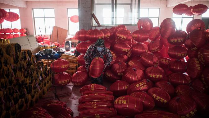 Seorang pekerja sedang melipat lampion merah menjelang perayaan Tahun Baru Imlek di provinsi Hebei, Tingkok (11/1). Dalam persiapan perayaan terbesar di Tiongkok ini, mereka membuat lampion selama lebih dari sebulan. (AFP Photo/Fred Dufour)