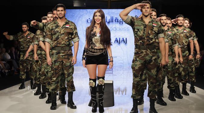 Perancang busana Suriah, Manal Ajaj berada di atas catwalk bersama model pria yang mengenakan seragam tentara Suriah di Beirut (11/10). (AFP Photo/Joseph Eid)