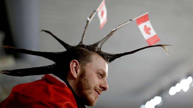 Seorang pria menata rambutnya dengan unik saat menyaksikan cabang curling antara Rusia dan Swiss pada Olimpiade Musim Dingin 2018 di Gangneung, Korea Selatan, Senin (12/2). Ada 92 negara peserta yang mengikuti ajang tersebut. (AP/Natacha Pisarenko)