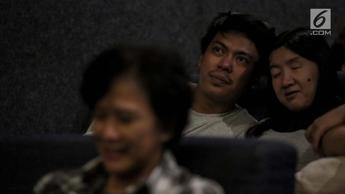 Relawan bisik menjelaskan alur film kepada penyandang tunanetra saat menyaksikan film di Bioskop Bisik di Pavilliun 28, Jakarta, Minggu (14/1). Kini, menonton bioskop bukan menjadi hal mustahil lagi bagi penyandang tunanetra. (Liputan6.com/Faizal Fanani)