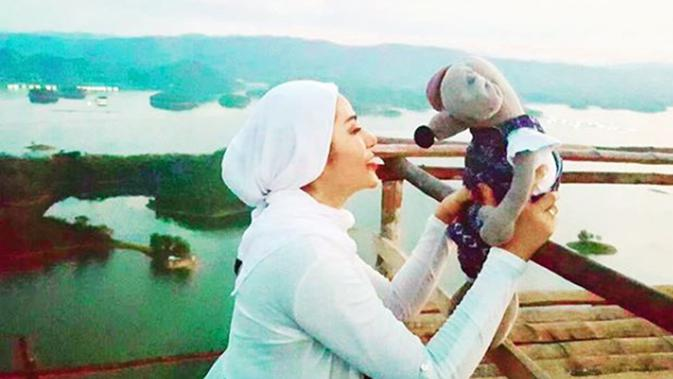 Selebritas Cinta Penelope berpose dengan sebuah boneka dengan latar belakang pemandangan alam. Banyak warga dunia maya yang memuji kecantikan Cinta Penelope lebih tampak setelah berhijab. (Instagram/princess_cinta_penelope)