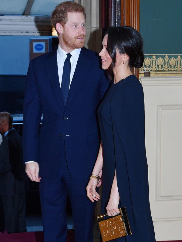 Pangeran Harry bersama tunangannya, Meghan Markle menghadiri konser perayaan ulang tahun Ratu Elizabeth di London, Sabtu (21/4). Di tangannya, Meghan memakai clutch box dari Naeem Khan dengan motif perbintangan. (ANDREW PARSONS/POOL/AFP)