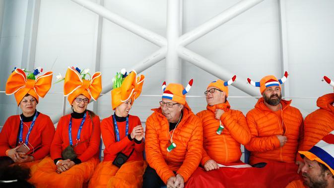 Penonton mengenakan atribut kepala unik saat menunggu dimulainya balapan speed skater 1.500 meter pada Olimpiade Musim Dingin 2018 di Gangneung, Korea Selatan, Selasa (13/2). Ada 92 negara peserta yang mengikuti ajang tersebut. (AP/John Locher)