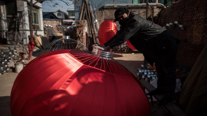 Seorang pekerja sedang merakit lampion merah yang akan dijual untuk menyambut perayaan Tahun Baru Imlek di provinsi Hebei, Tingkok (11/1). (AFP Photo/Fred Dufour)