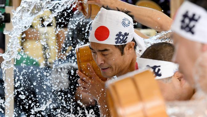 Penganut agama Shinto melakukan mandi air dingin di Kuil Kanda, Tokyo, Jepang (13/1). Upacara ini diawali dengan pemberkatan oleh pendeta. Acara dilanjutkan dengan lari pagi mengelilingi kuil. (AFP Photo/Toshifumi Kitamura)
