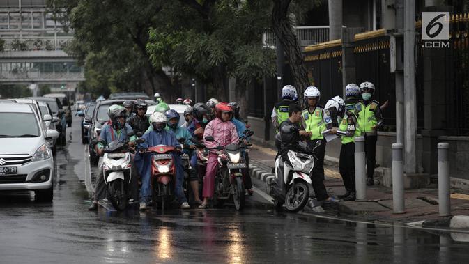 Polisi melakukan tindakan tilang kepada pengendara motor yang melanggar aturan jalur khusus di Jalan MH Thamrin, Jakarta Pusat, Kamis (8/2). Pengendara yang melanggar, ditilang dengan denda maksimal Rp 500 ribu. (Liputan6.com/Arya Manggala)