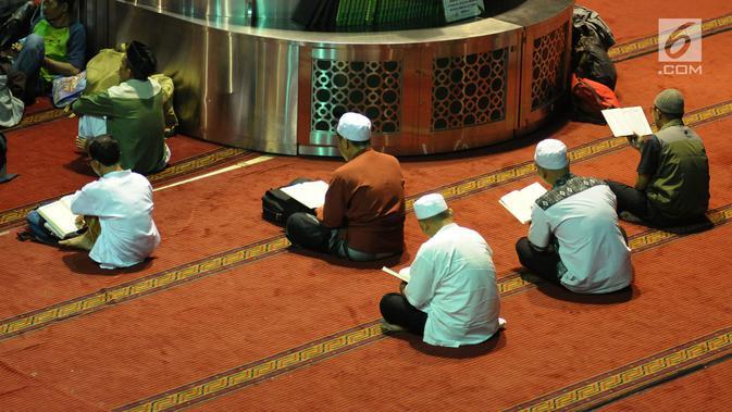 Umat muslim membaca Al-Quran secara berjamaah pada hari ke-28 bulan suci Ramadan di Masjid Istiqlal, Jakarta, Selasa (12/6). Sejumlah umat muslim meningkatkan ibadah mereka dengan melakukan itikaf di Masjid Istiqlal. (Liputan6.com/Helmi Fithriansyah)