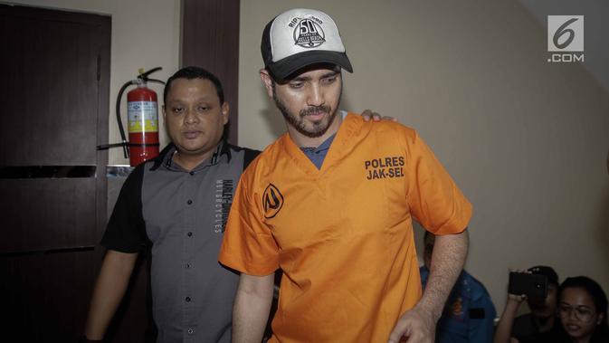 Aktor Fachri Albar dikawal petugas saat dihadirkan dalam gelar rilis di Polres Jakarta Selatan, Rabu (14/2). Selain itu ditemukan juga puntung ganja bekas pakai. (Liputan6.com/Faizal Fanani)