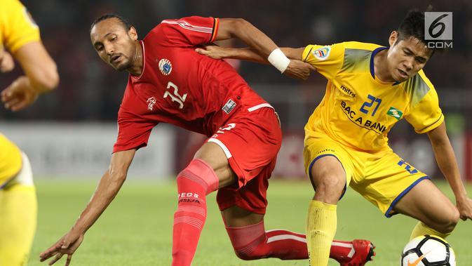 Gelandang Persija, Rohit Chand berebut bola dengan pemain Song Lam Nghe An pada fase grup H Piala AFC di Stadion GBK Jakarta, Rabu (14/3). Babak pertama Persija ditahan imbang Soang Lam Nghe An 0-0. (Liputan6.com/Helmi Fithriansyah)