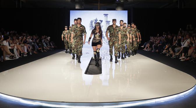Perancang busana Suriah, Manal Ajaj (tengah) berjalan di atas catwalk bersama model pria yang mengenakan seragam tentara Suriah di Beirut (11/10). (AFP Photo/Joseph Eid)