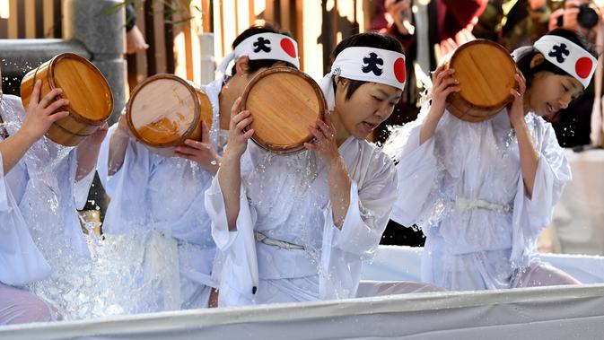 Sejumlah wanita penganut agama Shinto melakukan mandi air dingin di Kuil Kanda, Tokyo, Jepang (13/1). Upacara ini diawali dengan pemberkatan oleh pendeta. Acara dilanjutkan dengan lari pagi mengelilingi kuil. (AFP Photo/Toshifumi Kitamura)