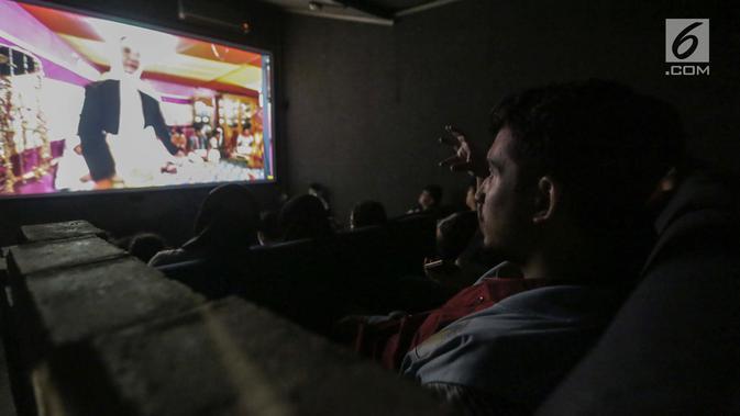 Penyandang tunanetra serius menyimak alur cerita yang diceritakan relawan bisik saat menyaksikan Bioskop Bisik di Pavilliun 28, Jakarta, Minggu (14/1). Penyandang tunanetra pun dapat merasakan emosi yang ada di film tersebut. (Liputan6.com/Faizal Fanani)