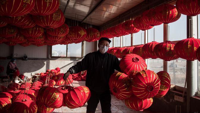 Pekerja membawa lampion yang sudah jadi untuk dijemur jelang perayaan Tahun Baru Imlek di provinsi Hebei, Tingkok (11/1). (AFP Photo/Fred Dufour)