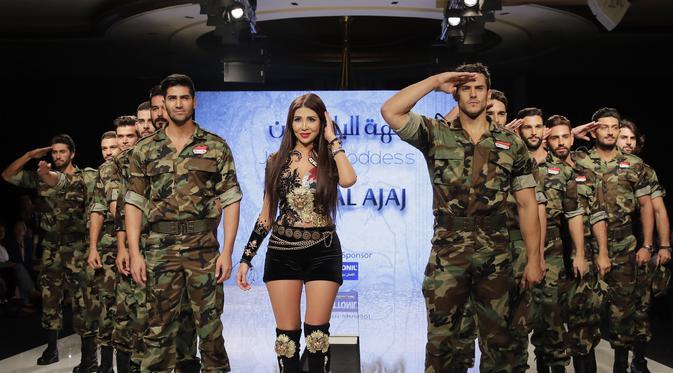 Perancang busana Suriah, Manal Ajaj (tengah) berpose di atas catwalk dengan model pria yang mengenakan seragam tentara Suriah di penghujung peragaan busananya yang bertema