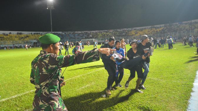 Salah seorang pendukung Arema FC digotong rekannya saat kericuhan duel Arema FC Vs Persib Bandung (Rana Adwa/Liputan6.com)