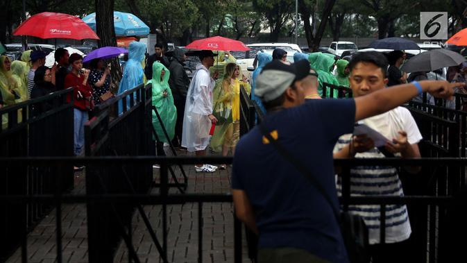 Sepasang muda mudi berteduh jas hujan saat mengantre tiket konser Liam Gallagher di Ecovention Ancol, Jakarta Utara, Minggu (14/1). Ariel NOAH, Rian D'MASIV, hingga Glenn Fredly menyatakan akan menghadiri konser ini. (Liputan6.com/JohanTallo)