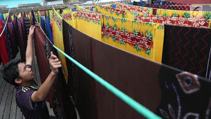 Pekerja menjemur kain sasirangan di kawasan Banjarmasin, Kalimantan Selatan, Senin (26/3). Proses pewarnaan kain ini dengan menggunakan bahan perintang seperti tali, benang atau sejenisnya menurut corak-corak tertentu. (Liputan6.com/Immanuel Antonius)
