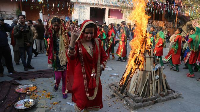 Gadis-gadis India berpakaian tradisional menari mengelilingi api unggun saat merayakan festival Lohri di Jammu, India (13/1). Dimana siang hari sangat pendek dan malam hari sangat panjang pada hari itu. (AP Photo / Channi Anand)