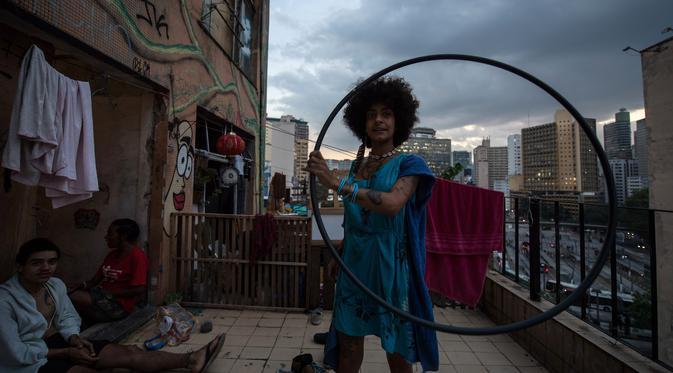Seorang wanita bermain hula hoop di teras gedung 'Ocupa Ouvidor 63' di Sao Paulo, Brasil (28/6). Dapat dikatakan gedung tersebut kini menjadi salah satu  pusat seni di kota Sao Paulo. (AFP Photo/Nelson Almeida)