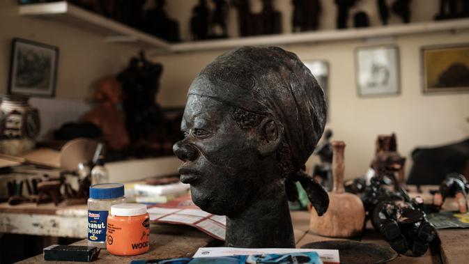 Bentuk patung karya Edward Njenga yang diberi nama 'Women's Guild Member (2008)' dipajang di bengkelnya, Nairobi, Kenya, Senin (12/3).  Ketika bekerja, Njenga biasa dibantu oleh cucu yang memiliki nama sama dengannya. (AFP PHOTO/Yasuyoshi CHIBA)