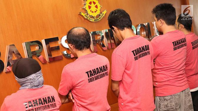 Anggota The Family Muslim Cyber Army diperlihatkan di Dittipid Siber Bareskrim Polri, Jakarta (28/2). Enam tersangka, satu di antaranya wanita ditangkap karena menyebarkan berita bohong yang meliputi kebangkitan PKI. (Liputan6.com/Immanuel Antonius)