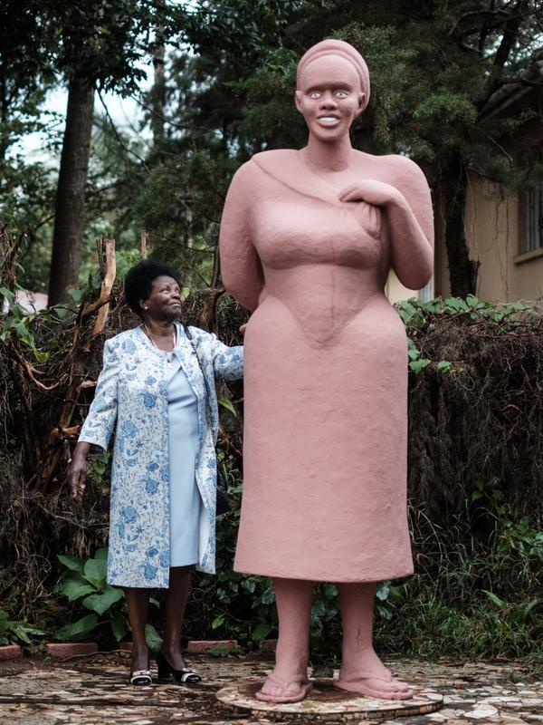 Istri pematung Edward Njenga, Hannah Njenga berdiri di samping karya sang suami yang diberi nama 'Mama Ngina' di rumah mereka di Nairobi, Kenya, Senin (12/3). (AFP PHOTO/Yasuyoshi CHIBA)