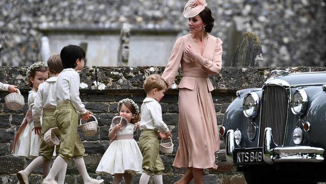 Kate Middleton menggandeng anak keduanya, Puteri Charlotte, berjalan bersama Pangeran George (Reuters Photo)