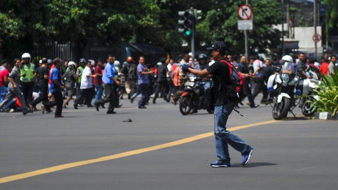 Di tengah kepanikan pasca ledakan di Jalan Thamrin, Jakarta, seorang pria yang diperkirakan berusia antara 20-30 tahun, berpakaian kaos dan bertopi hitam serta membawa ransel merah, tiba-tiba mengeluarkan senjata, Kamis (14/1). (REUTERS/Veri Sanovri/Xin)