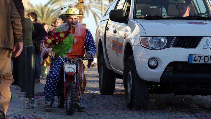 Seorang pria mengenakan kostum badut sambil menaiki sepeda motor mini saat mengikuti Parade Karnaval Clowns di pantai Sesimbra, Lisbon, Spanyol (12/2). (AP Photo / Armando Franca)